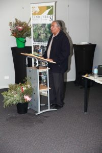 George Walley standing at lectern speaking