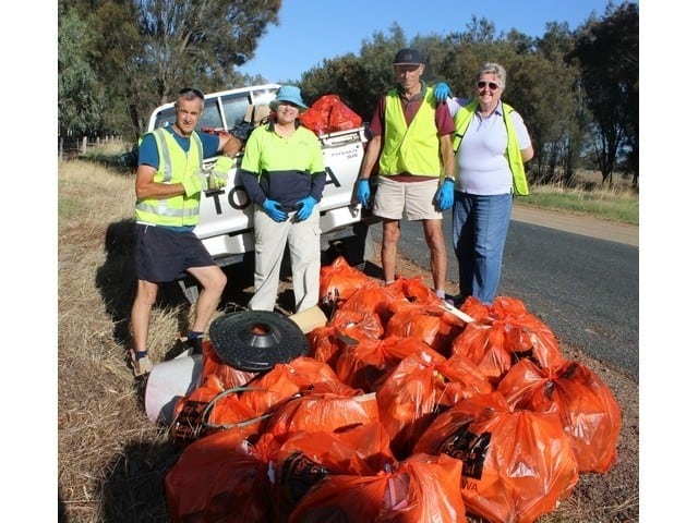 People standing next to bags of garbage collected on Clean Up Australia Day