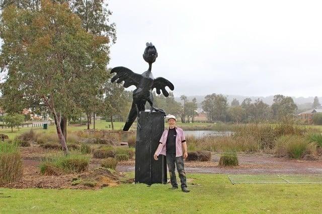 Artist Len Zuks standing next to Black cockatoo sculpture in Byford, Western Australia