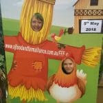 Perth Royal Show volunteers with head in a photoboard showing a scarecrow and a chicken.