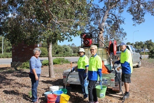 four members of Byford Enviro-link watering plants at the Byford information bay