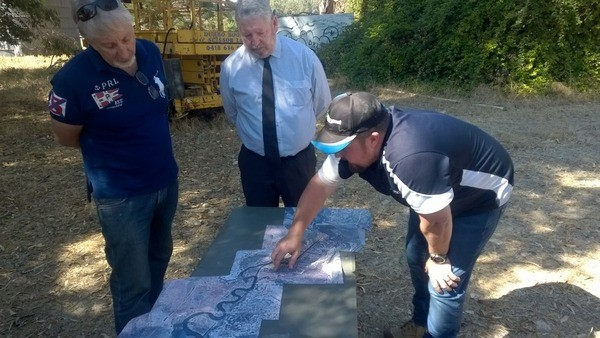Three men pointing to map of river