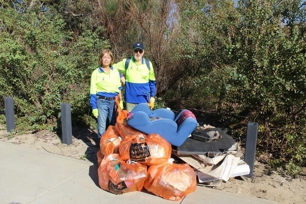 two people standing by bags of rubbish collected at a reserve in Byford