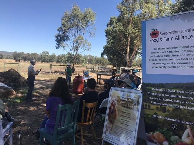people sitting in a paddock listening to someone speaking