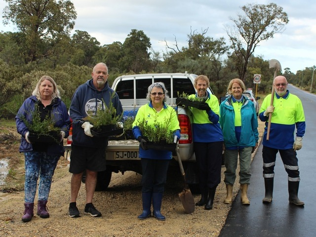men and women standing infront of a ute holding seedlings